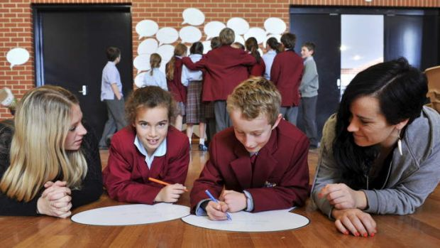 Anti-bullying presenters, Rosie Thomas, left and her sister, Lucy, with year 5 students, Alice Humphries, 10, of ...