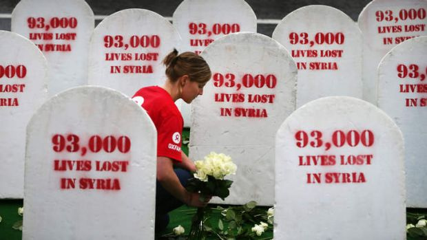 An Oxfam worker in Belfast places roses among rows of gravestones symbolising the 93,00 people killed in Syria. The ...