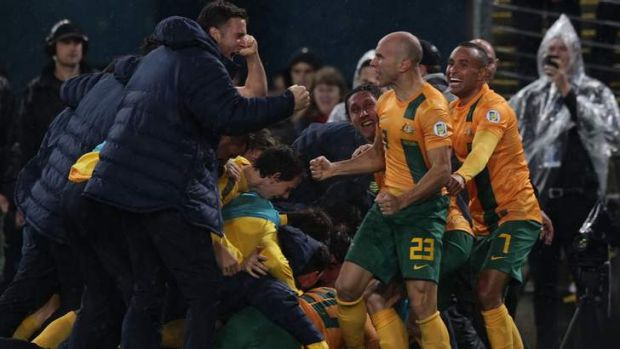 Party time: Socceroos players celebrate Josh Kennedy's goal.