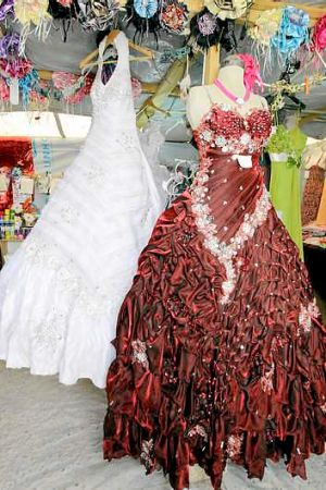 Wedding gowns hang in a covered stall in the Zaatari refugee camp.