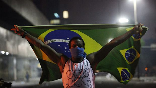 A masked protester holds a Brazilian flag during protests in downtown Rio de Janeiro.