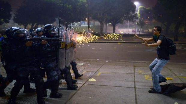 In the line of fire: A demonstrator is shot by rubber bullets after clashes erupted during a protest in Rio de Janeiro.