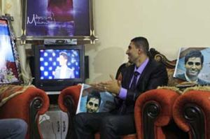 Shadi, the brother of Palestinian singer Mohammad Assaf, watches the final of the <i>Arab Idol</i> competition in ...
