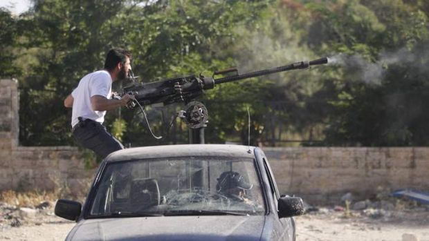 A Free Syrian Army fighter fires a machine gun on the front line in Aleppo.