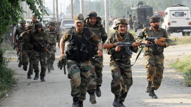 Indian army soldiers run towards the scene of a deadly attack by armed rebels on the outskirts of Srinagar on June 24, 2013.