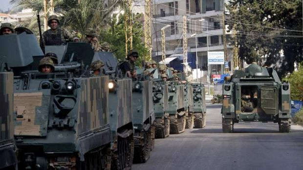 Lebanese army vehicles move toward the site of clashes between followers of a radical Sunni cleric Sheik Ahmad al-Assir ...