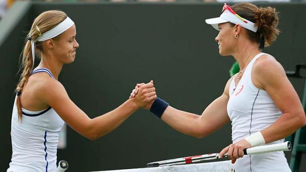 Samantha Stosur shakes hands with Anna Schmiedlova after defeating her in their women's singles match at Wimbledon on ...