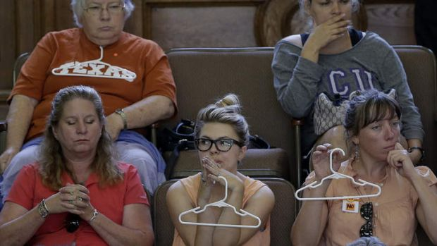 Opponents to an abortion bill sit in the senate chamber as Wendy Davis speaks.