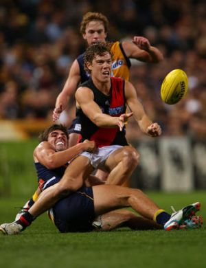 Caught: Essendon's Jake Melksham gets a handball away as he is tackled by Andrew Gaff.
