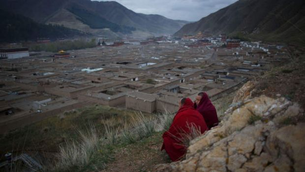 Two monks sit on a hillside overlooking the Labrang monastery in Xiahe, Gansu province, a flashpoint for many Tibetan ...
