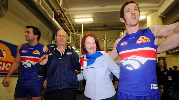 Julia Gillard joins (from left) Brian Lake, coach Rodney Eade and Robert Murphy in singing the song after the win over ...