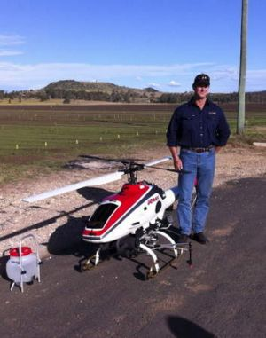 Greg Harris with an RMAX unmanned helicopter that he is leasing for weed spraying.