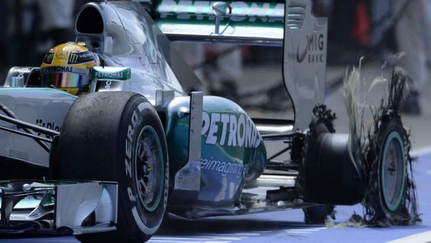 Mercedes Formula One driver Lewis Hamilton of Britain enters the pit with an exploded tyre.
