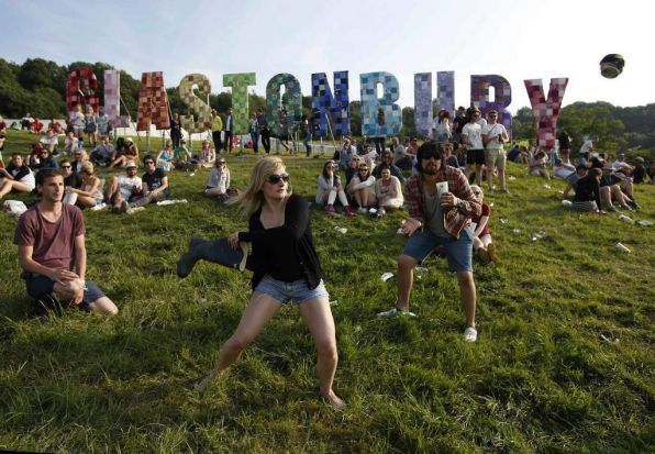 Festival goers play rounders with a wellington boot and a beer can on the first day of Glastonbury music festival.