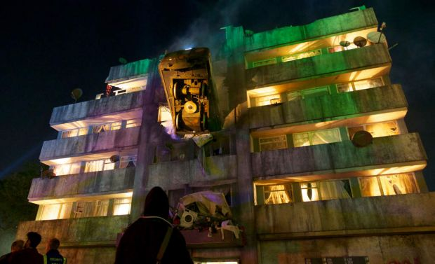 The exterior of a Glastonbury bar made in the form of a block of flats with a London Underground train crashed into it.