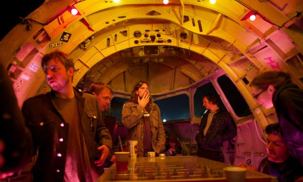 Glastonbury festivalgoer drinking in a bar made out of a cockpit of an aeroplane.