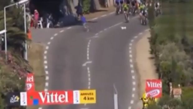 Mad dash ... a dog and a man flee the centre of the road as the Tour de France peloton bears down.