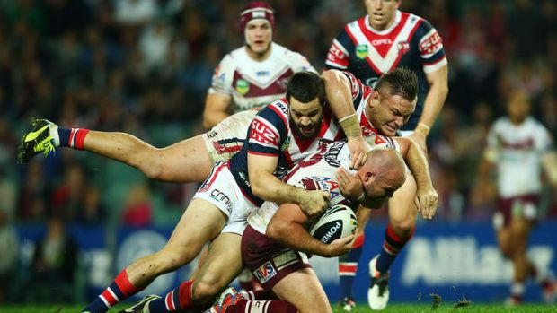 Double safety: Glenn Stewart of the Eagles is tackled by Aidan Guerra and Jared Waerea-Hargreaves of the Roosters.