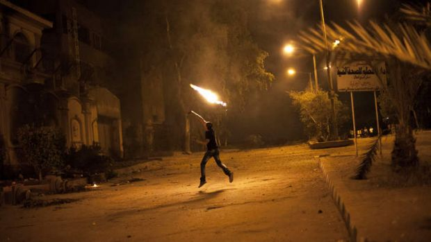 President under siege: An Egyptian protester attacks the Muslim Brotherhood headquarters in Cairo.