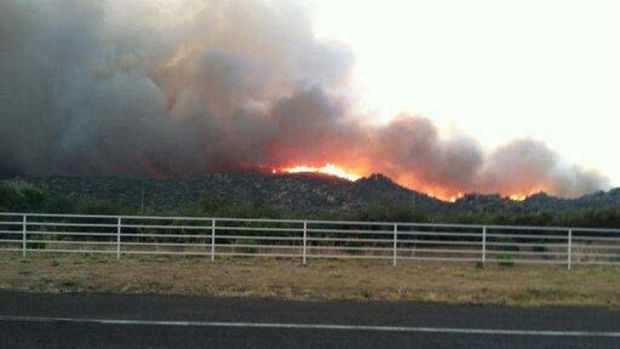 The Yarnell Hill fire is seen burning in this view from Highway I-17 near Yarnell, Arizona, in this handout photo taken ...