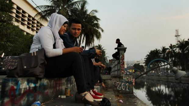 A couple sit at a canal in Jakarta's old quarter, where historic buildings await renovation.