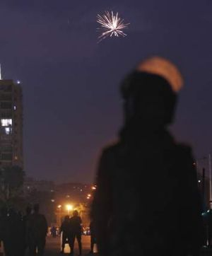 Fireworks are seen as army soldiers take their positions in front of protesters.