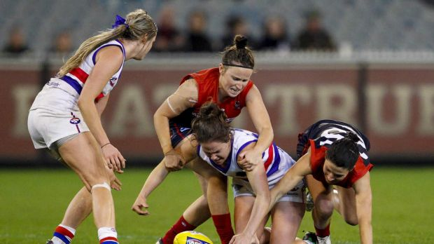 Emma Kearney (centre) of the Western Bulldogs competes for the ball against Melbourne in the inaugural AFL women's match ...
