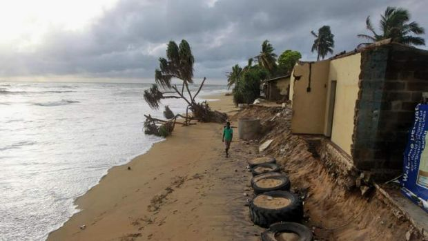 Living on the edge: A Sri Lankan man walks past a house damaged by sea erosion in Colombo.