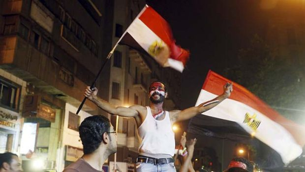 Celebration: An anti-Mursi protester dances in delight after the removal from office of Egypt's deposed President ...