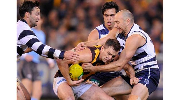 Swamped: Hawk Brian Lake is tackled by Cats James Podsiadly and Jimmy Bartel (left), watched by teammate Allen Christensen.
