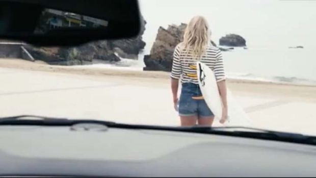 The woman then gets in a car before arriving at the beach with her surfboard.