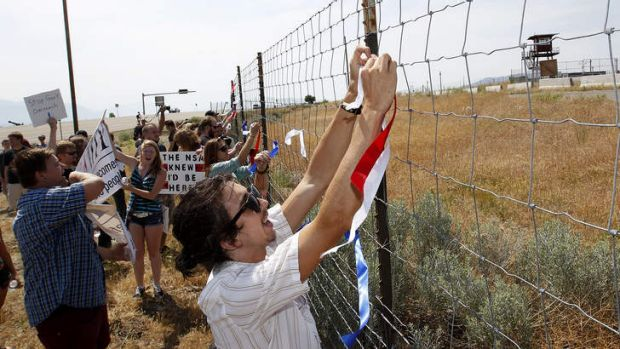 Protesters tie red, white and blue ribbons to the fence of a National Security Agency facility being built in Utah.