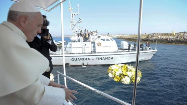 Remembering migrants lost at sea: Pope Francis throws flowers into the sea from a boat on Lampedusa.
