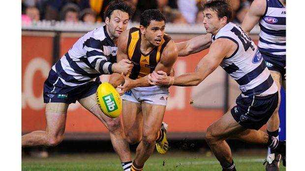 Geelong's Jimmy Bartel and Corey Enright give Hawthorn's Cyril Rioli no respite at the MCG.