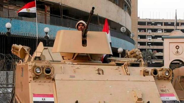 Egyptian troops guard the state TV building in Cairo.
