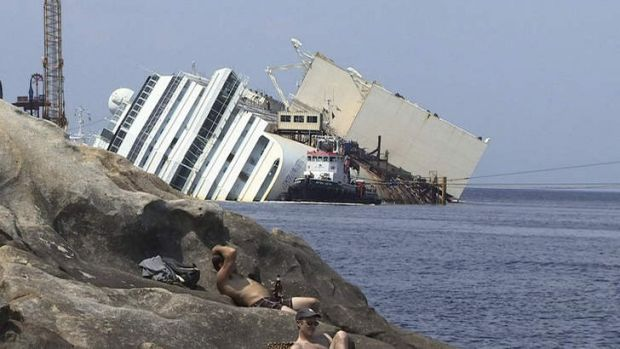 People sunbathe on the rocks as the wreckage of the Costa Concordia cruise ship is seen in the background, on the Tuscan ...