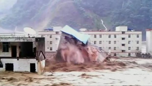 A building collapses amid a flood caused by torrential rain in Deyang City, Sichuan Province.