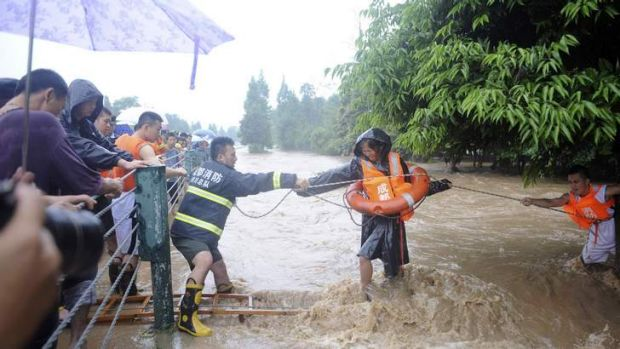 Firefighters use a rope to help a woman walk across floodwaters after heavy rainfalls hit Dujiangyan, Sichuan.