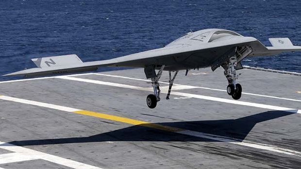 An X-47B drone combat aircraft lands on the deck of the USS George H.W. Bush aircraft carrier.