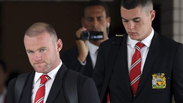Wayne Rooney, left, arrives in Bangkok on Thursday.