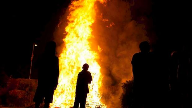People are silhouetted against the flames from a bonfire in Killyleagh, Northern Ireland.