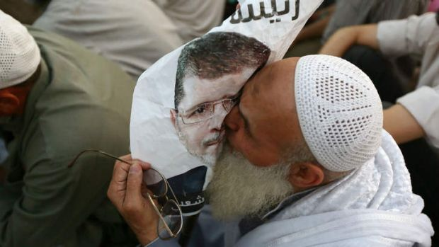 Ramadan tensions: An Egyptian supporter of ousted president Mohammed Mursi kisses a poster as worshippers gather for a ...