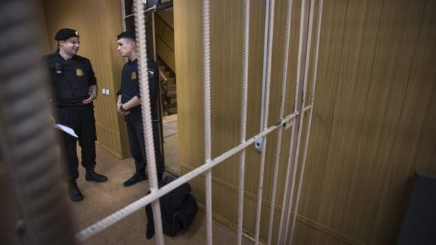 Show trial: Court officials stand beside an empty cage before the posthumous trial of Sergei Magnitsky