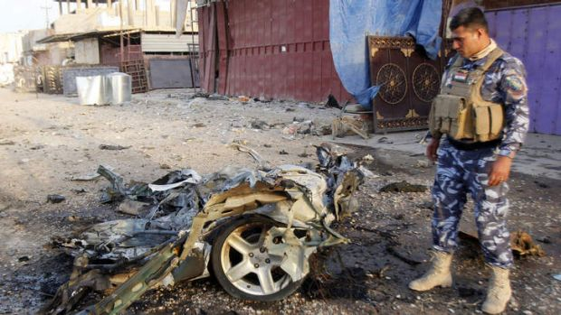 An Iraqi soldier inspects the wreck of a car bomb after it exploded in the military zone of the northern Iraqi city of ...