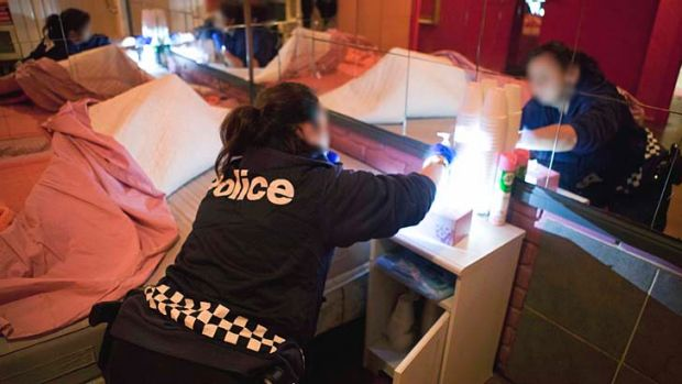 A police officer searches a room at a Melbourne brothel.