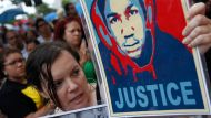 Annette Quintera from Miami holds an image of Trayvon Martin at a rally in Miami, Florida July 14, 2013. U.S. President ...