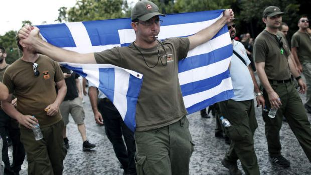 A police officer holds a Greek flag as he takes part in an anti-austerity rally during a 24-hour general strike in ...