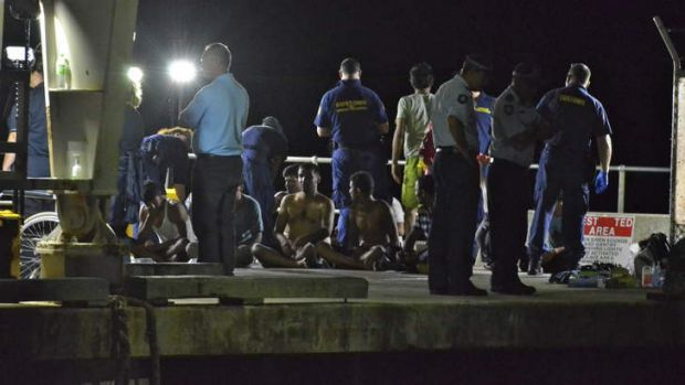 Customs officials and rescue personnel watch over survivors of the capsized boat at Christmas Island docks on Tuesday night.