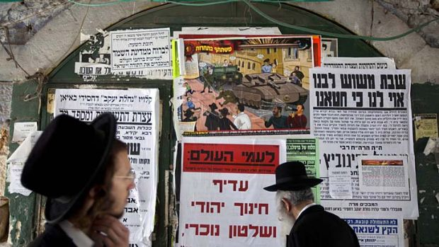 Ultra-Orthodox Jewish men walk past a poster in the Jewish Mea Shearim neighborhood in Jerusalem. A large cartoon poster ...
