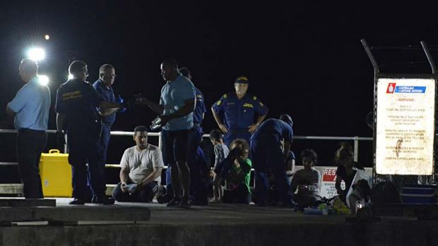 Heavy toll: Customs officials watch over survivors at Christmas Island earlier this week.